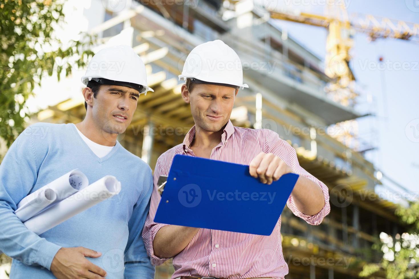 arquitectos varones con planos y portapapeles trabajando en el sitio foto