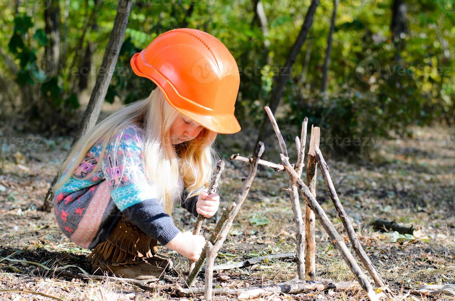 Chica con casco ensamblando palos en el suelo foto