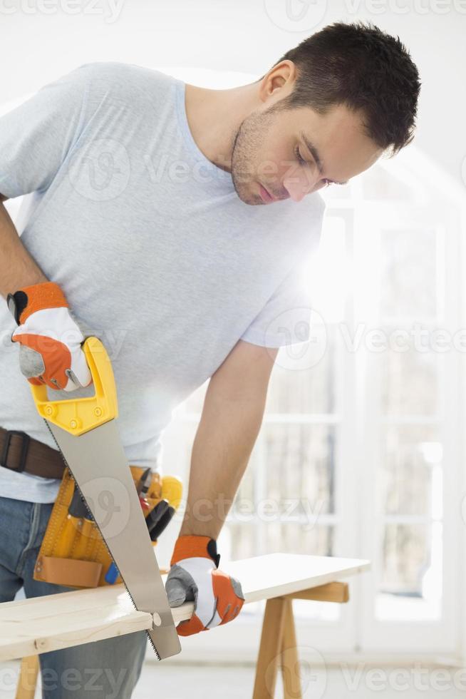 hombre aserrar madera en casa nueva foto