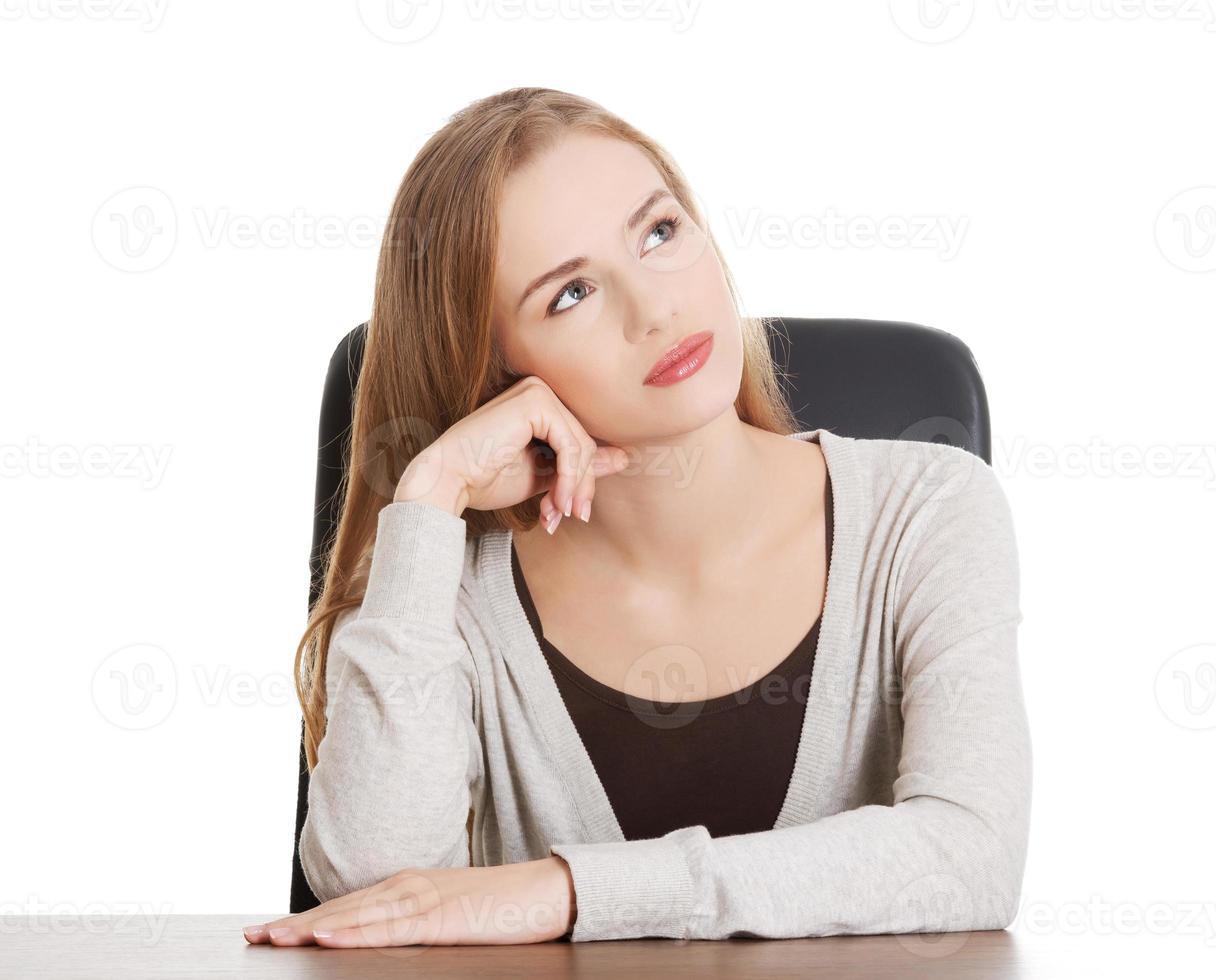 hermosa mujer casual sentada junto a un escritorio y soñando despierto. foto