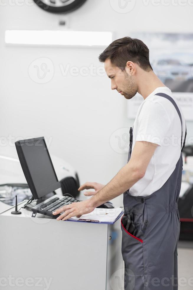 Vista lateral del mecánico de automóviles usando la computadora en el taller foto