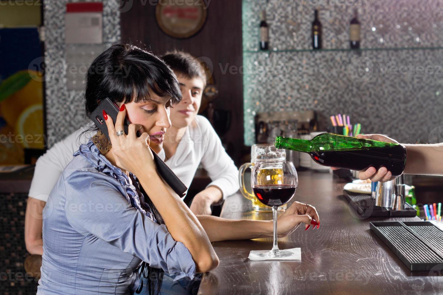 mujer chateando en su celular en el bar foto