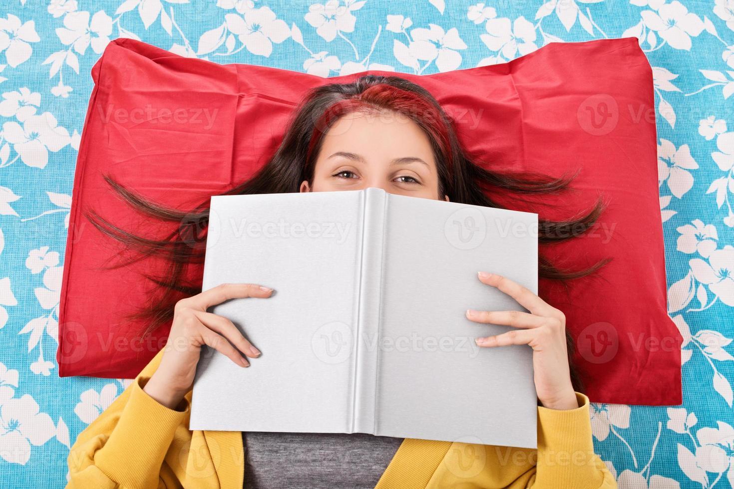 niña en la cama escondiendo su rostro detrás de un libro foto