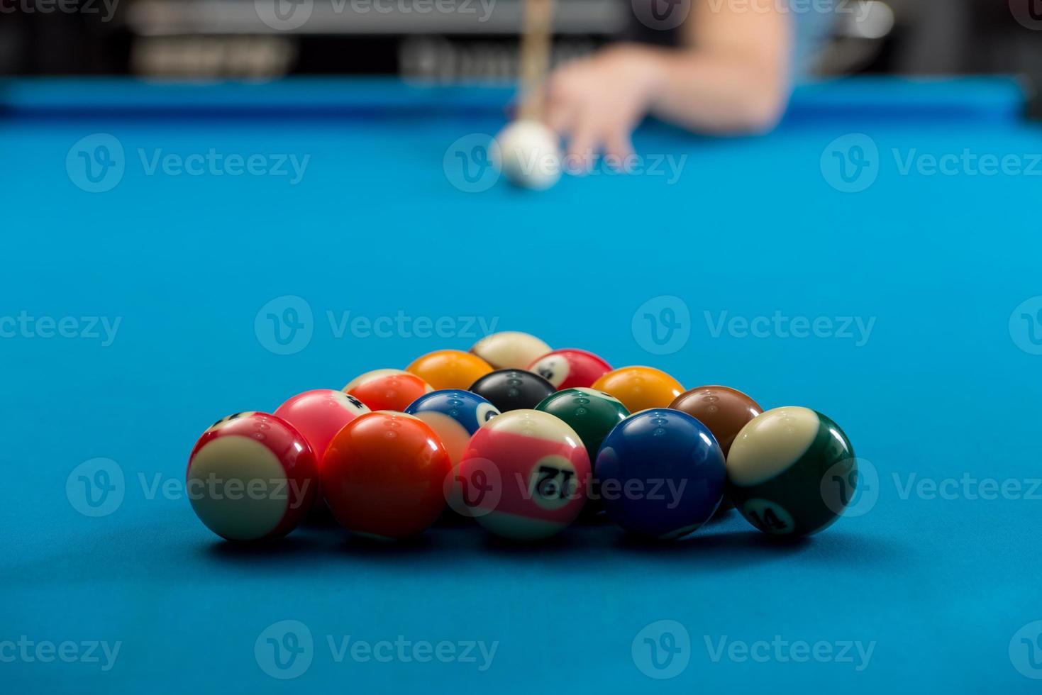 hombre jugando al billar a punto de golpear la pelota foto