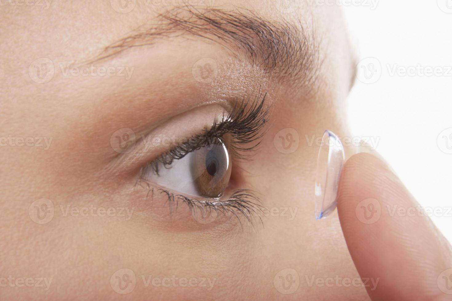 mujer poniendo en lentes de contacto foto