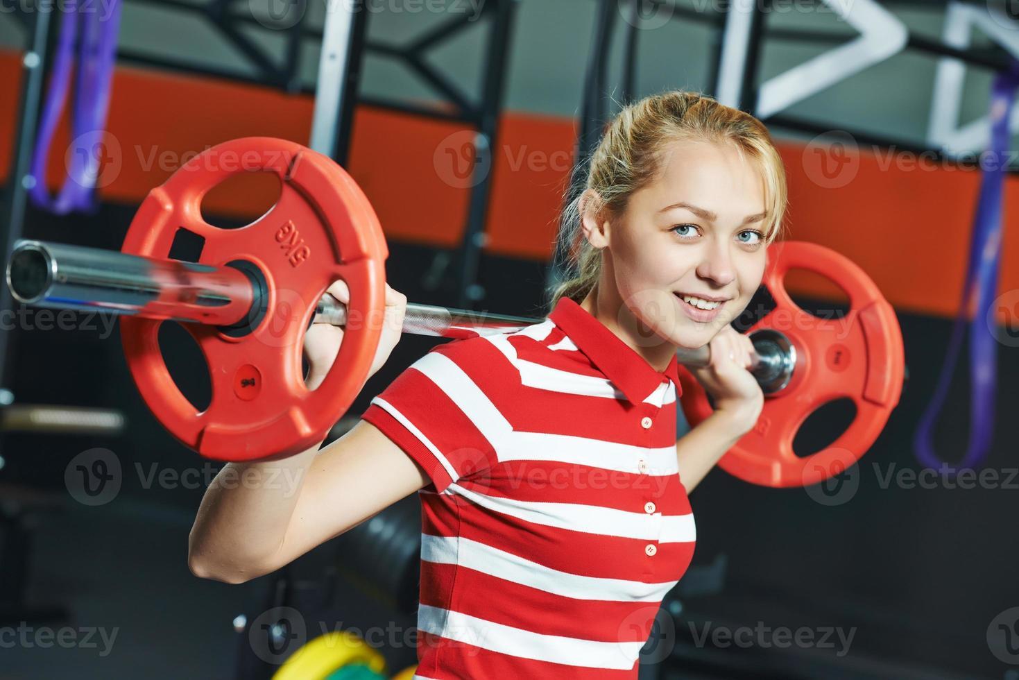 mujer con barra de pesas en el gimnasio foto