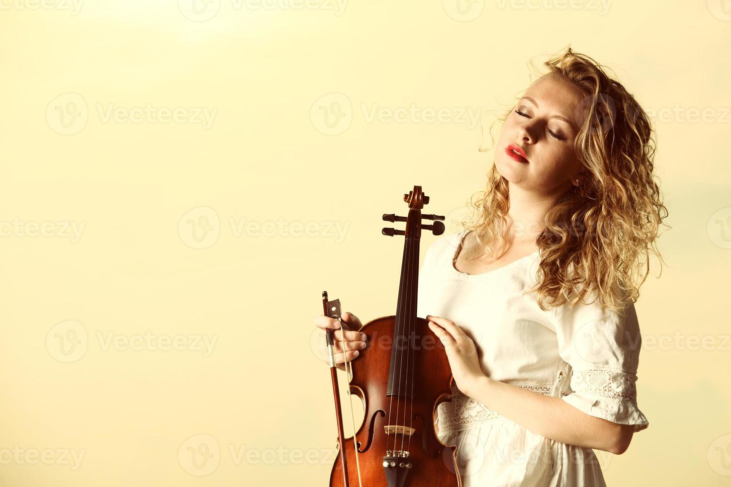 la chica rubia con un violín al aire libre foto