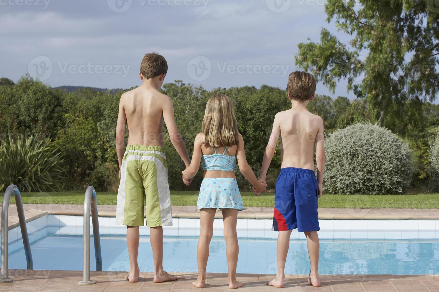 dos niños y niñas al borde de la piscina foto