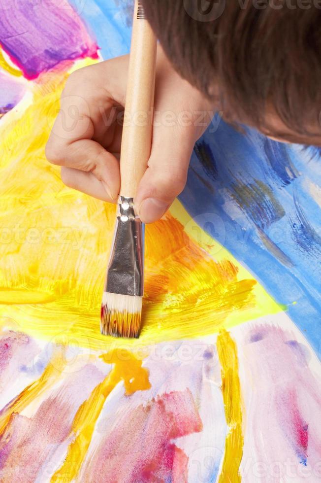 Cerca del niño con pincel para crear una escena al atardecer foto