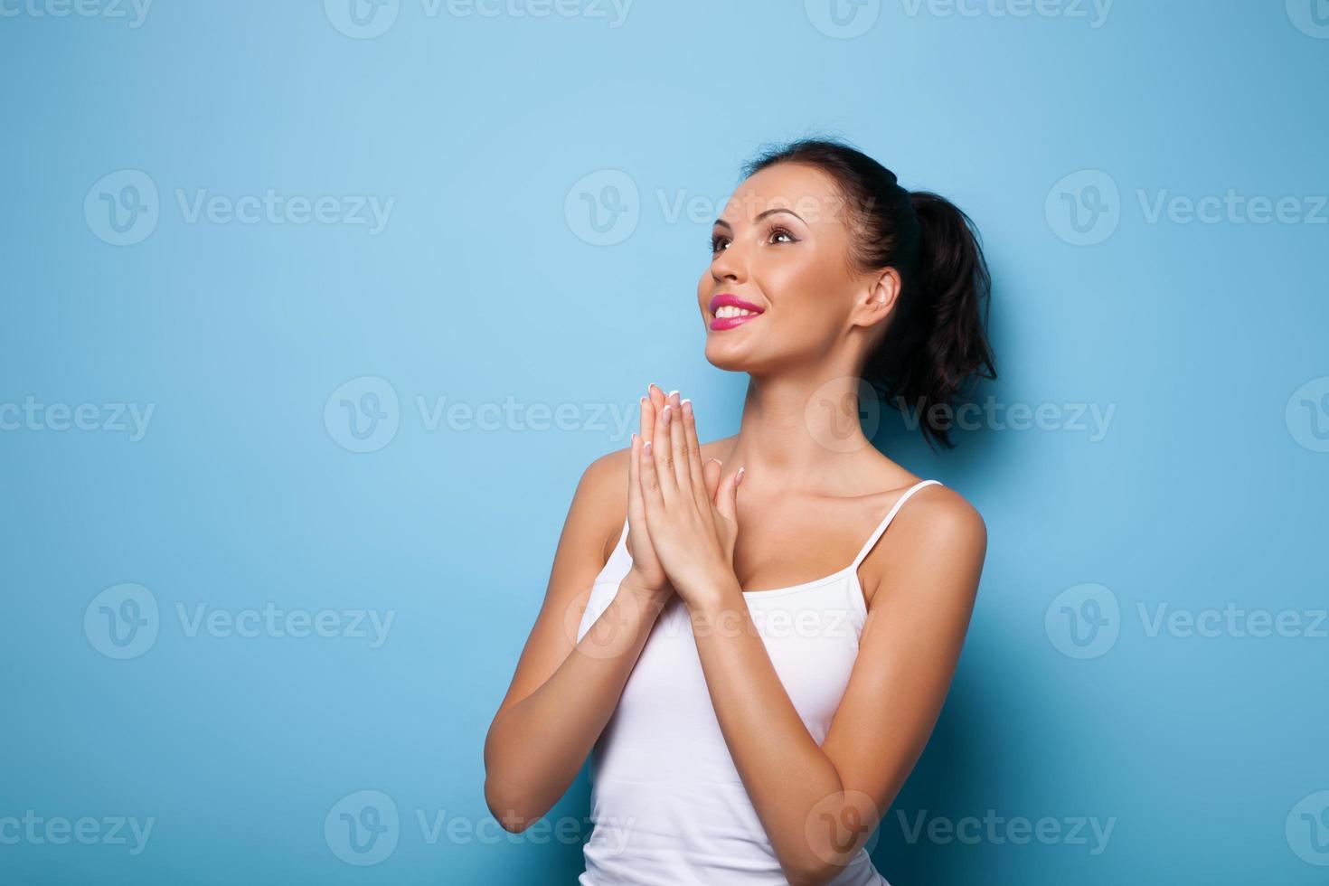 joven atractiva está rezando por buena suerte foto