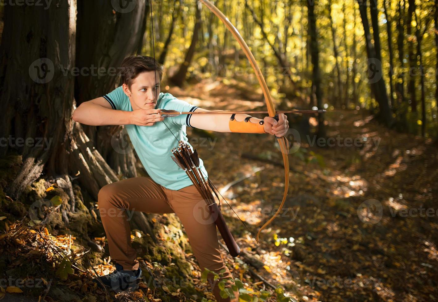 Man training in wood with bow and arrow. photo