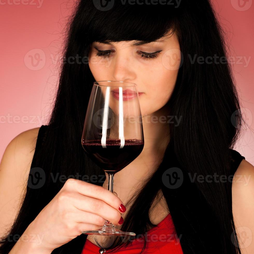 Beautiful young woman holding a glass of red wine photo