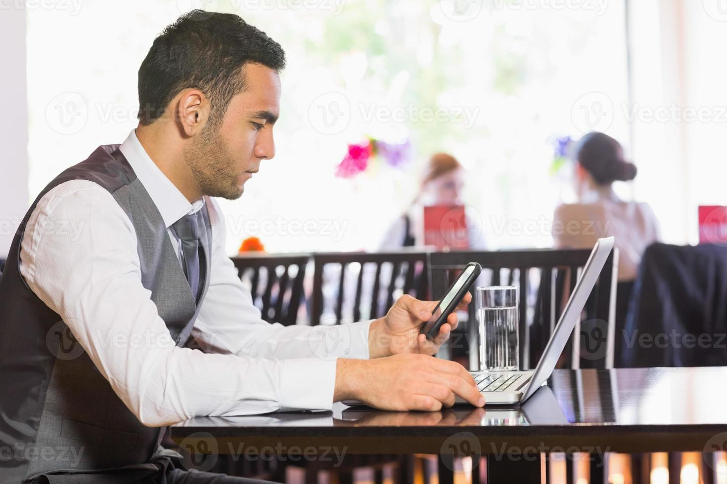 Serious businessman using phone while working on laptop photo