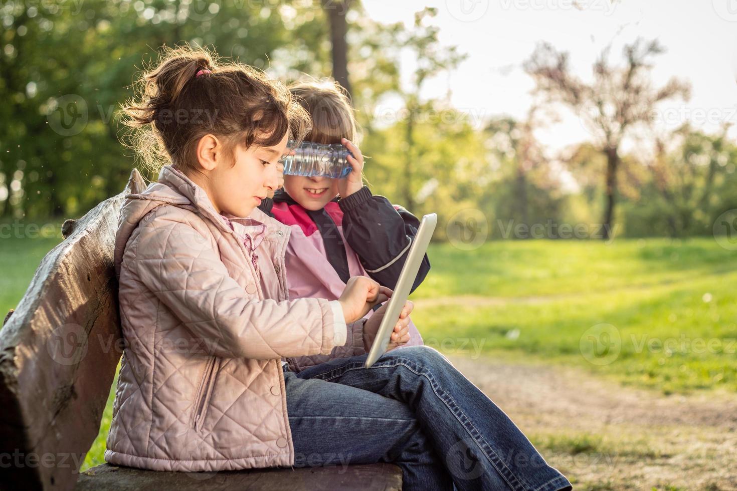 Foto de dos niñas usando tableta en el banco