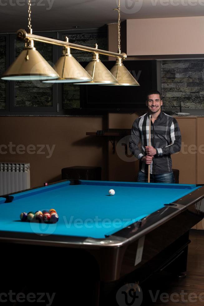 Retrato de un joven jugando billar foto
