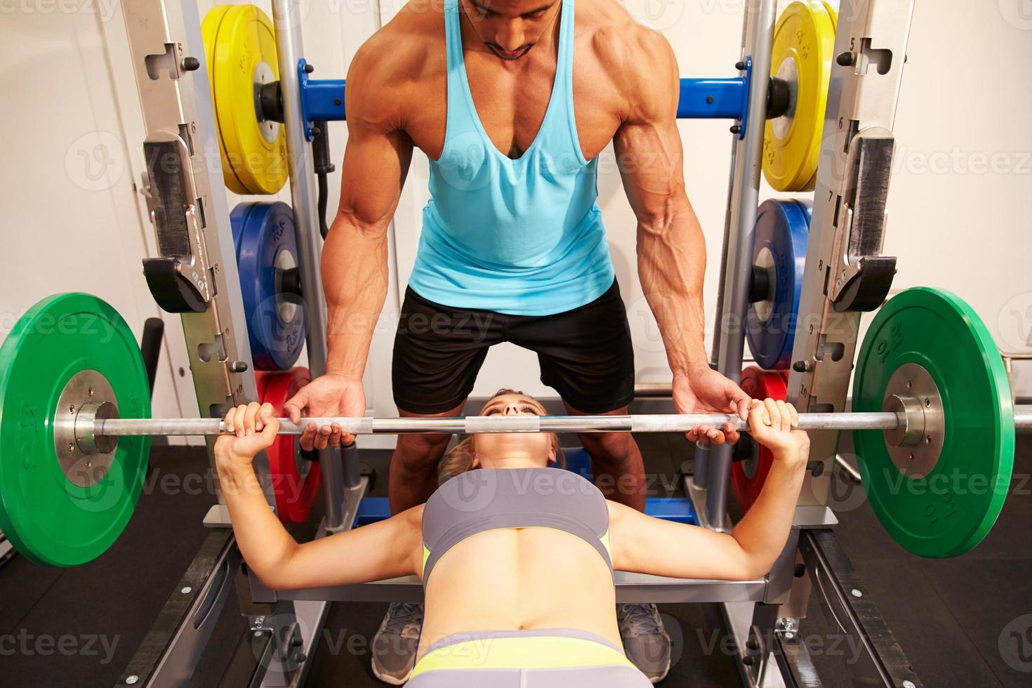 Woman bench pressing weights with assistance of trainer, front v photo