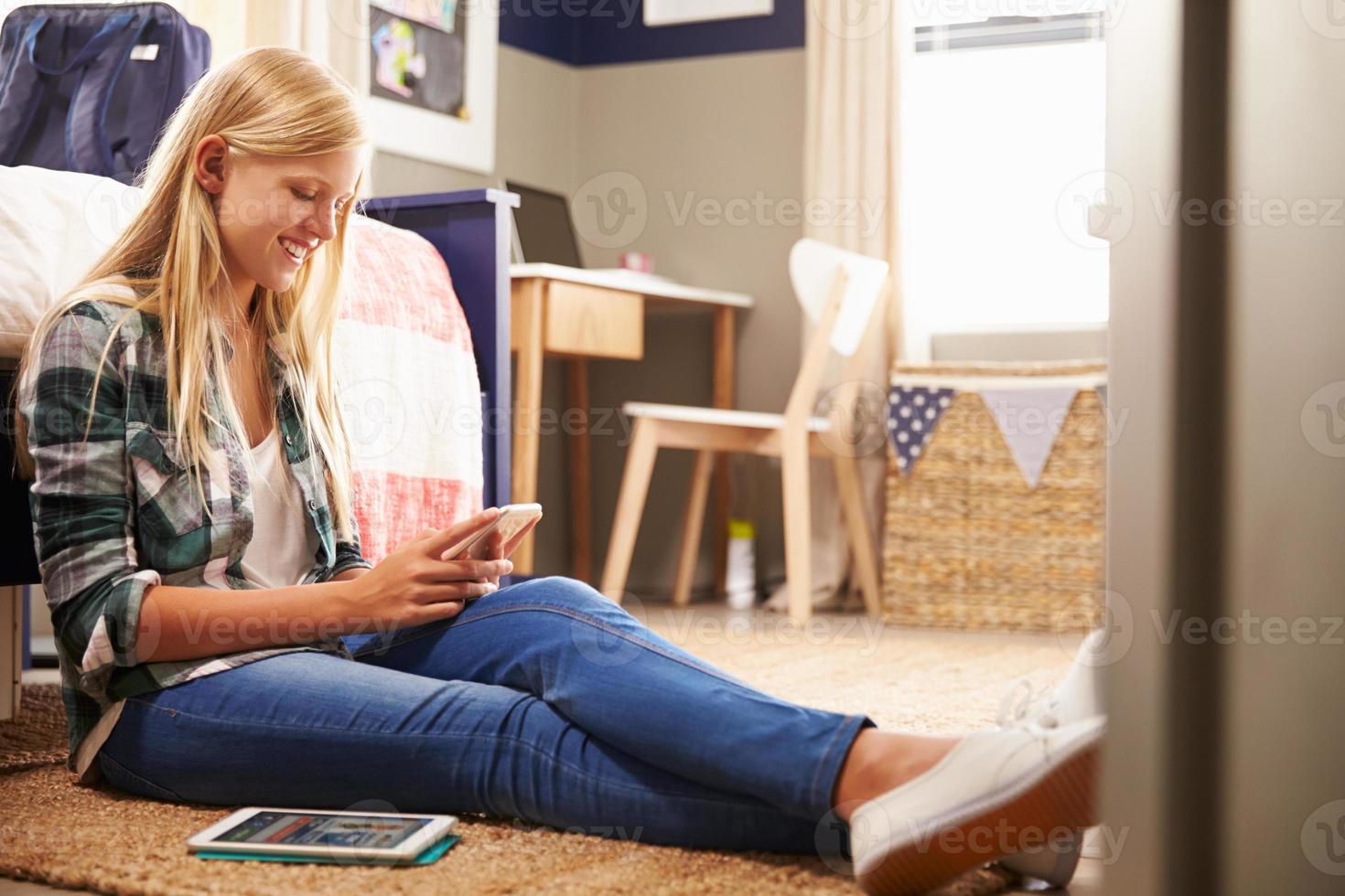 niña utilizando teléfonos inteligentes en su habitación foto