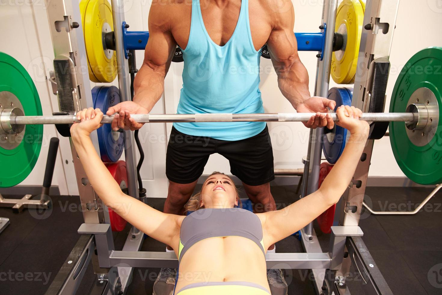 Woman bench pressing weights with assistance of trainer photo