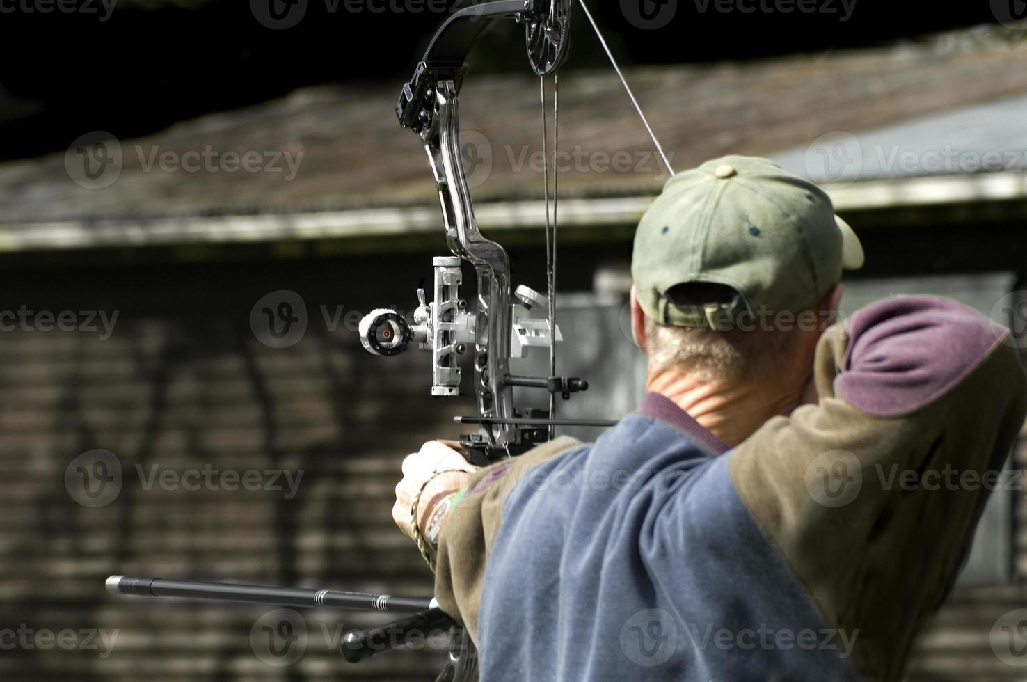 la espalda de un arquero a punto de disparar su arco y flecha foto
