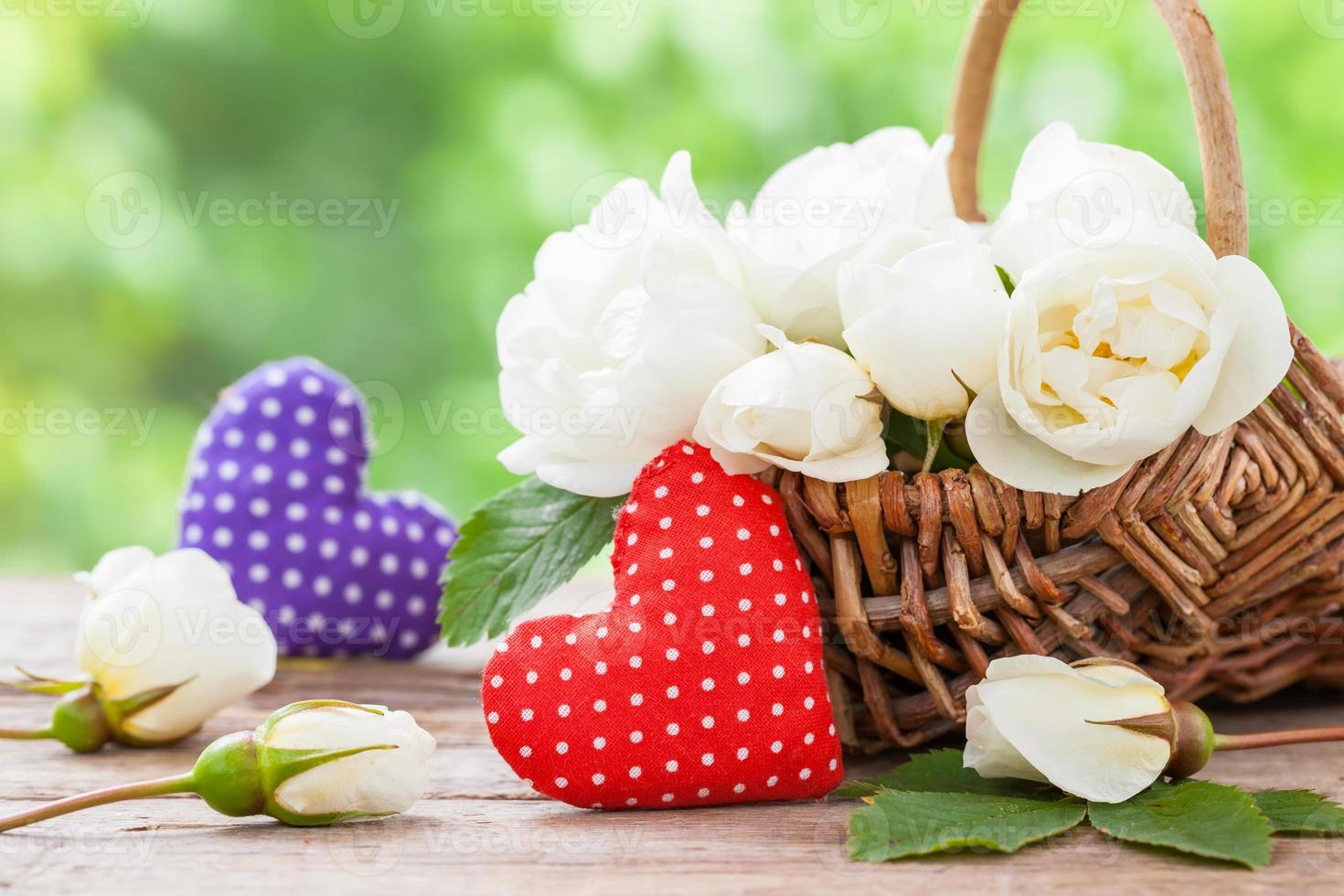 Wicker basket with wild rose flowers and two hearts. photo