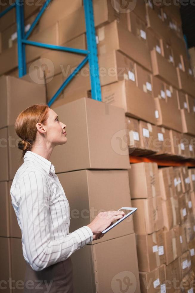 Female manager using digital tablet in warehouse photo