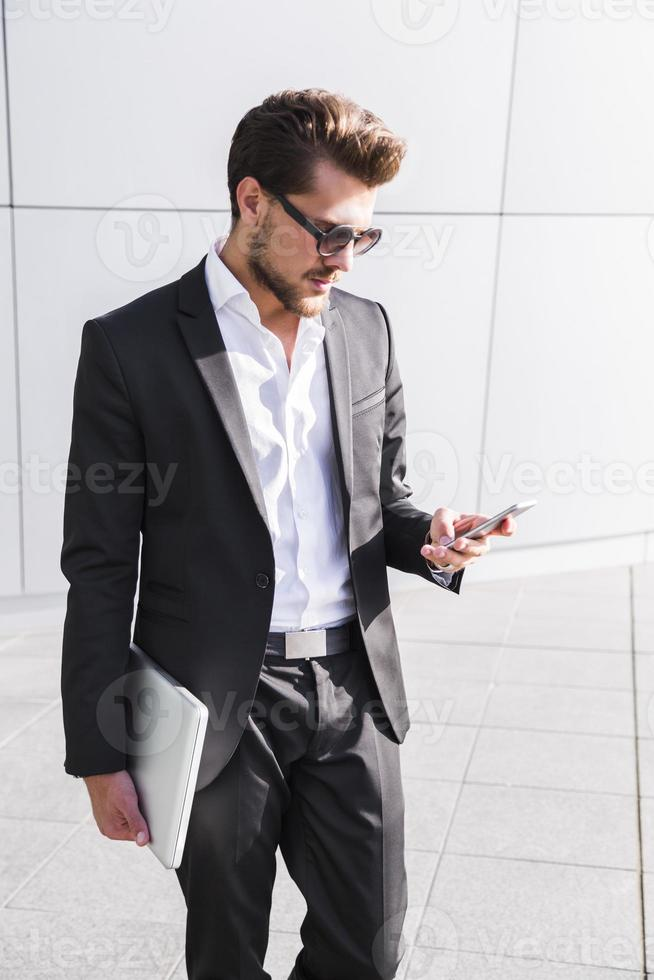 Male businessman or worker in black suit with smart phone photo