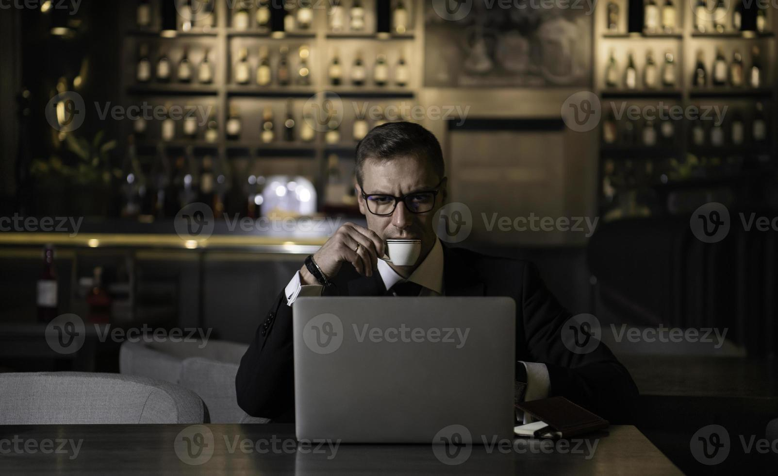 Serious handsome elegant caucasian businessman  sitting at moder photo