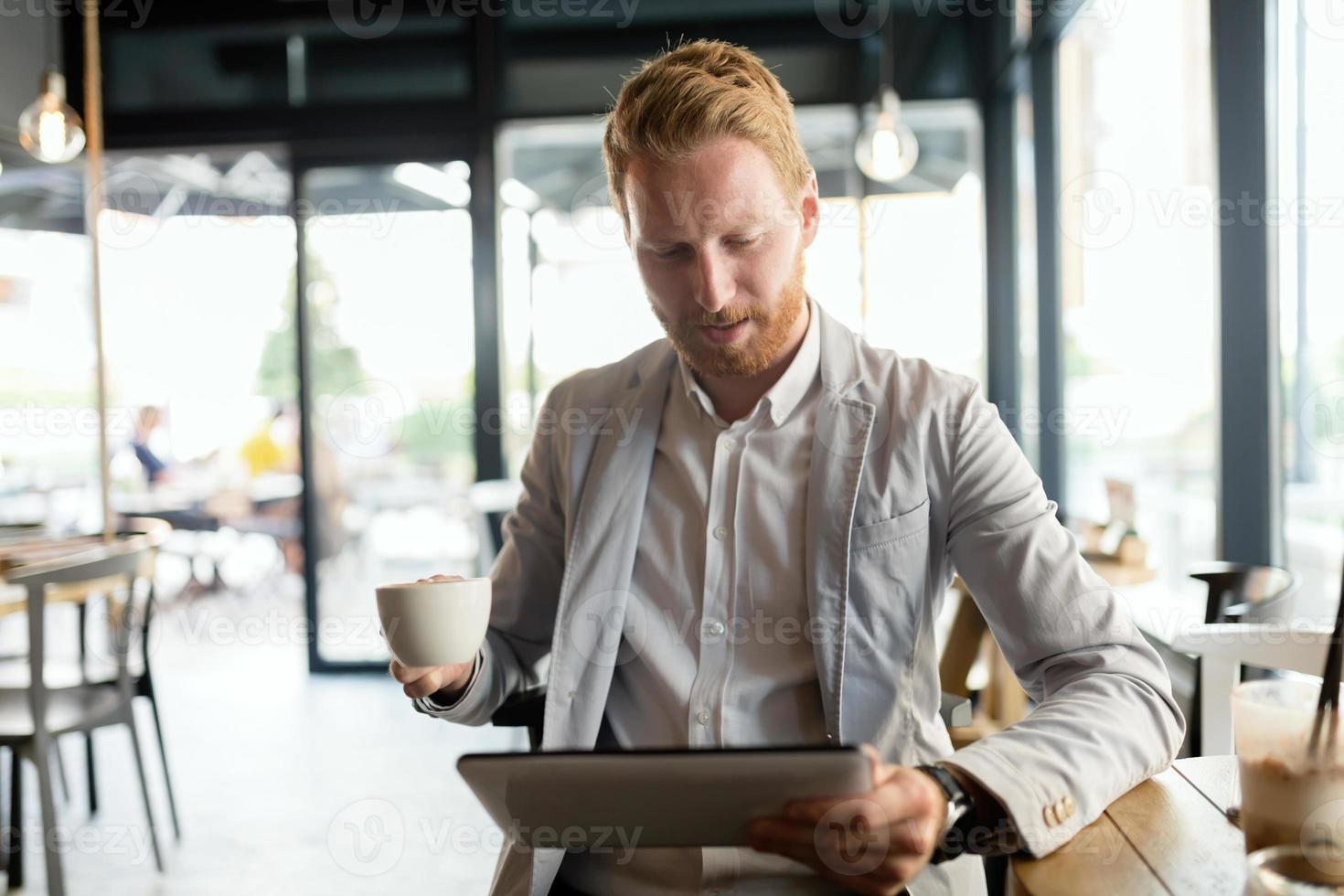 empresario ocupado disfrutando de un café mientras está en línea foto