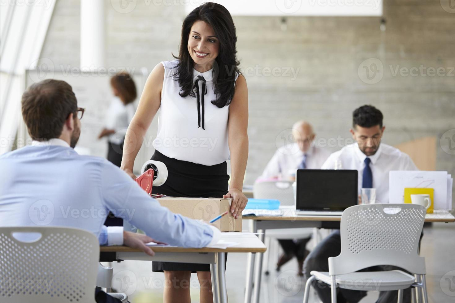 Businesswoman In Office Preparing Package For Shipping photo