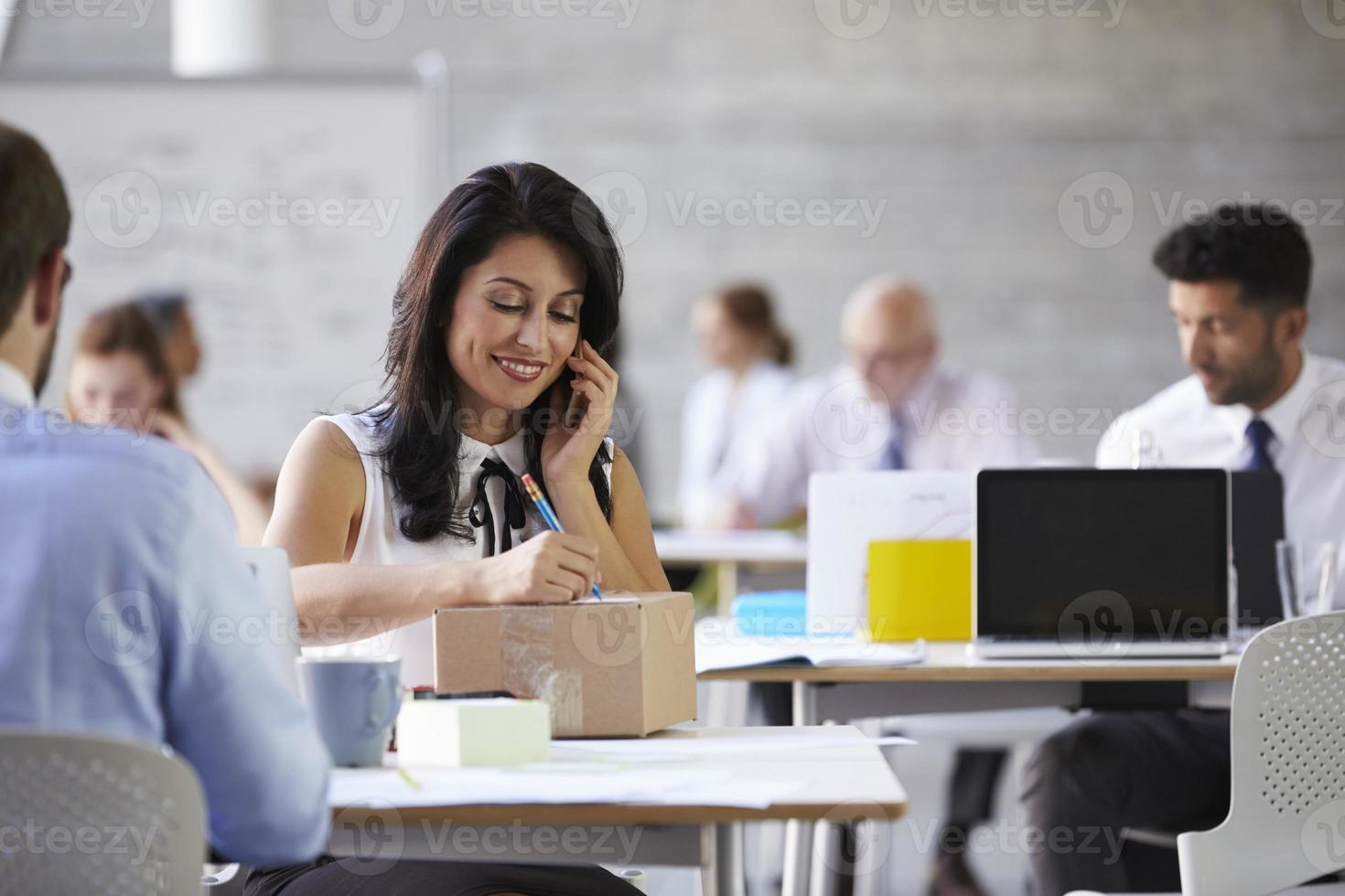 Businesswoman On Phone Arranging Collection Of Package photo