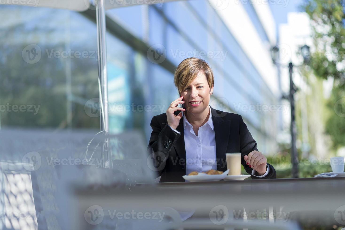 Portrait of a business woman sitting relaxed at outdoor cafe photo