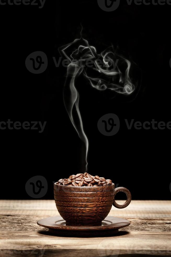 Wooden cup with beans and woman-shaped smoke photo