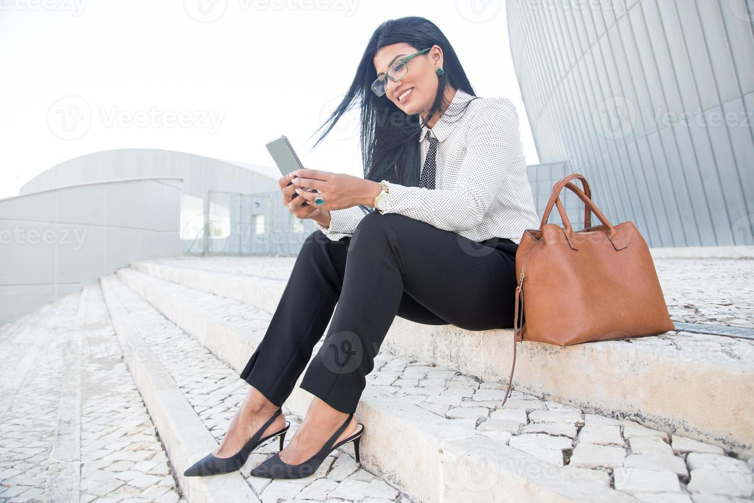 Positive young businesswoman using gadget for work photo