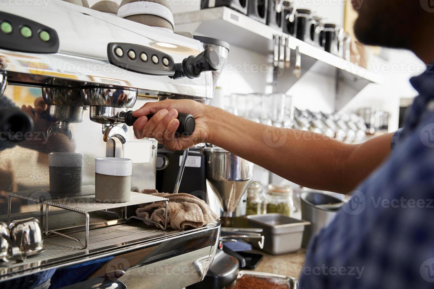 Young male barista preparing espresso at a cafe, close up photo