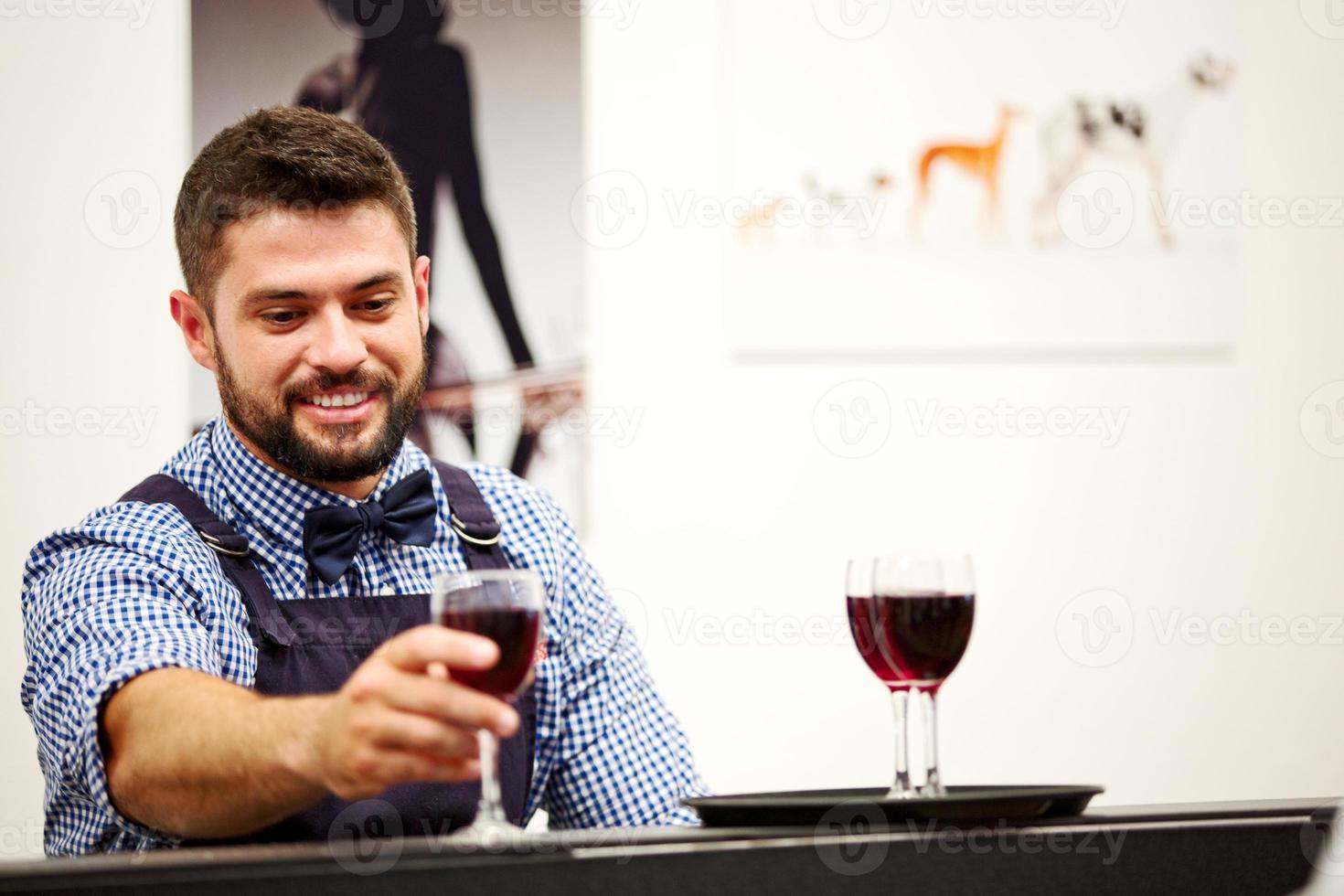 barman sirviendo vino tinto en copas en una función foto