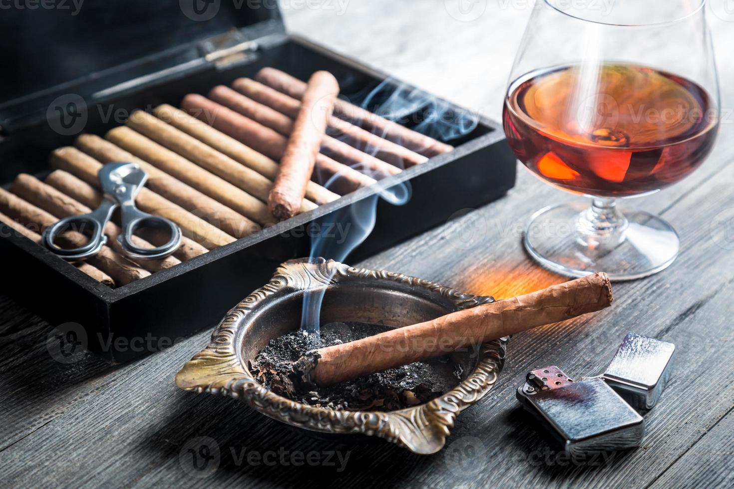Aroma of cognac and cigar fuming photo