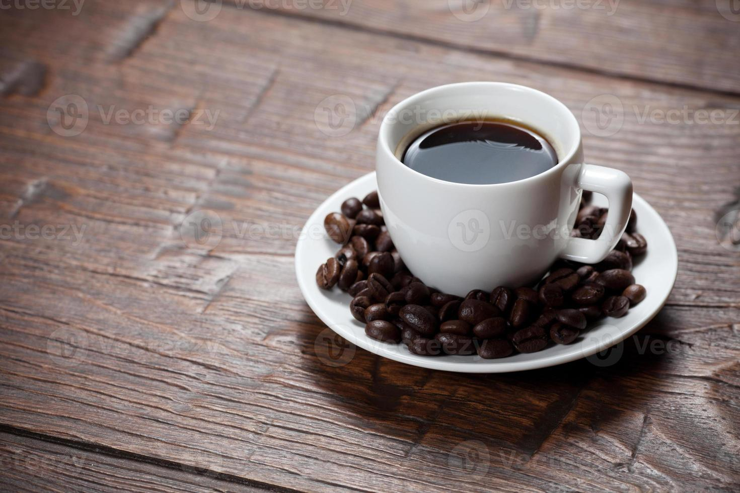 Taza de café y platillo en la mesa de madera foto