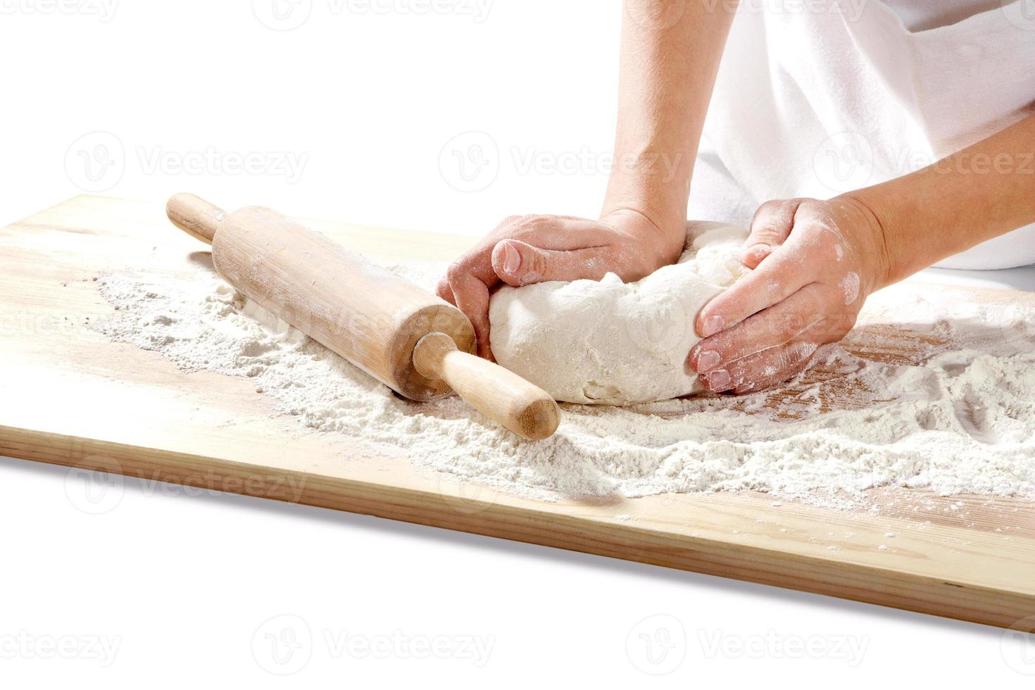 hands kneading dough on  board photo