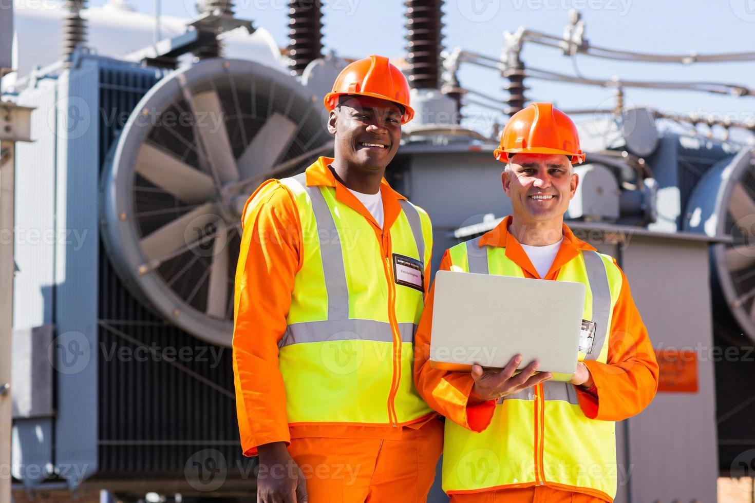 ingenieros eléctricos con laptop frente a transformador foto