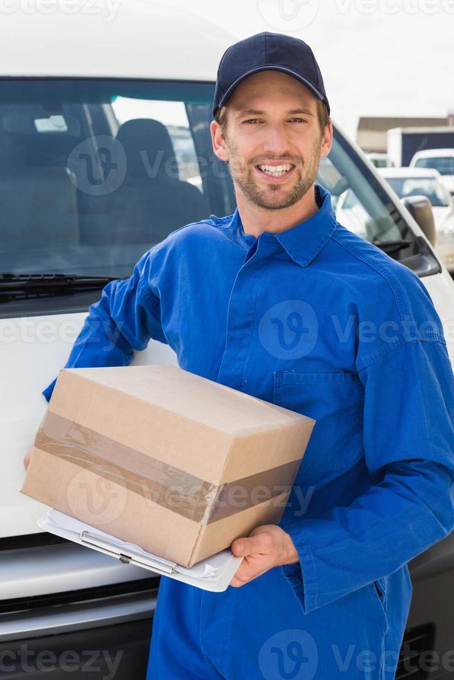 repartidor sonriendo a la cámara por su furgoneta con paquete foto
