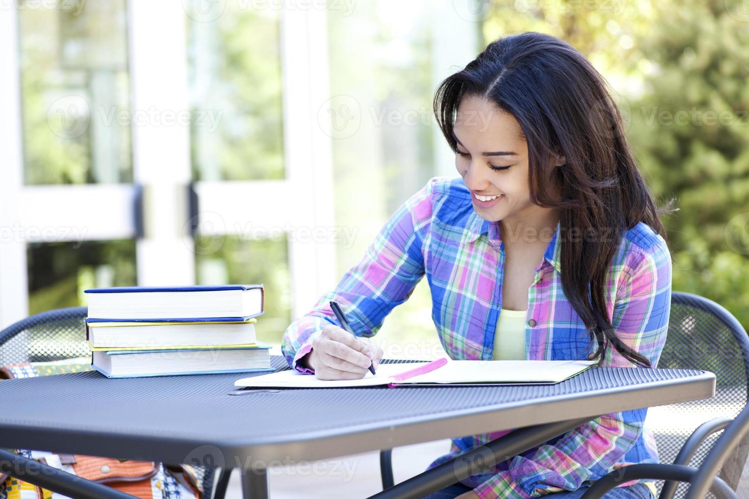 Ethnic student writing and studying with many books photo