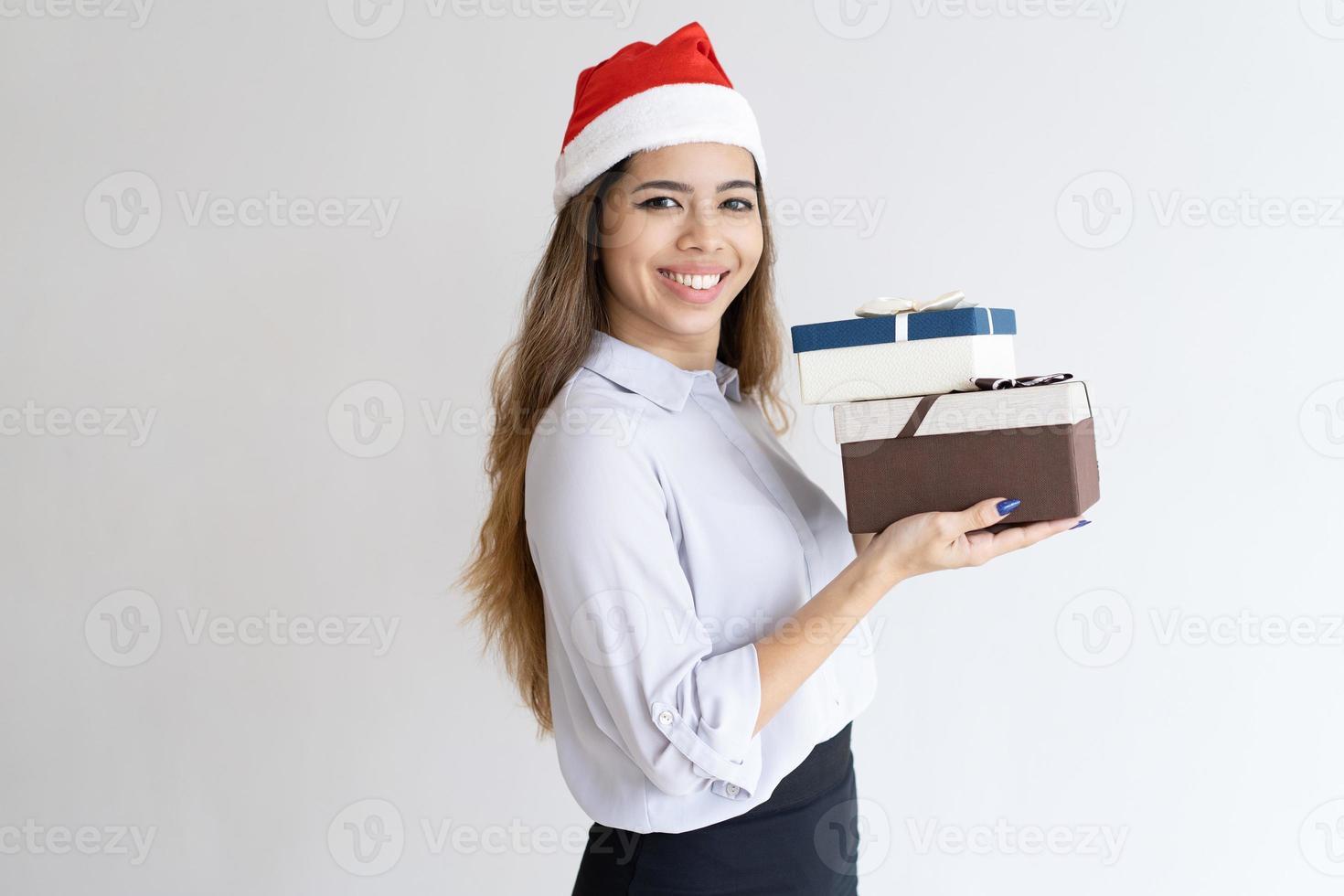 sonriente ayudante de oficina de navidad llevando regalos foto