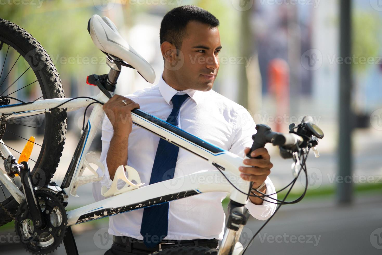 Handsome Hispanic Office Worker Carrying His Bike photo