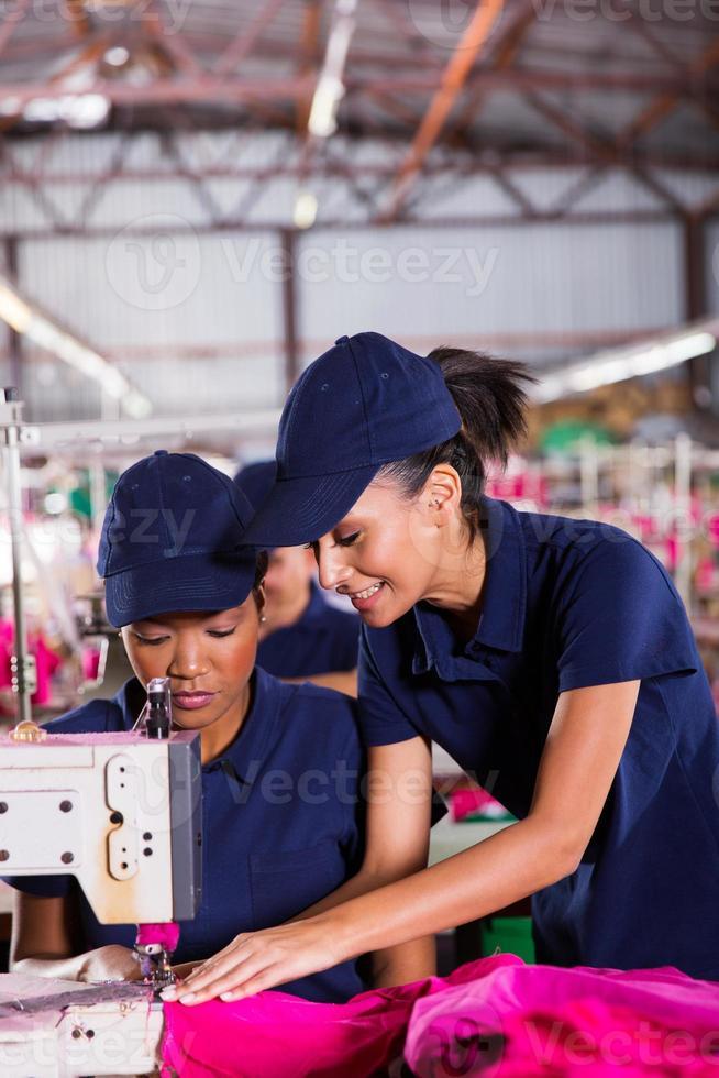 joven enseñando a nuevo maquinista a coser foto
