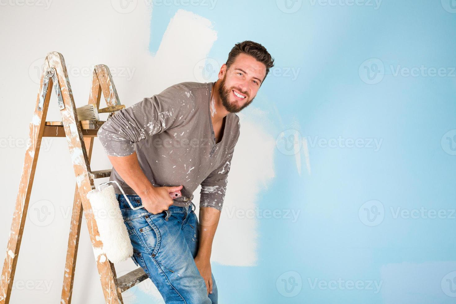 painter in paint splattered shirt painting a wall photo