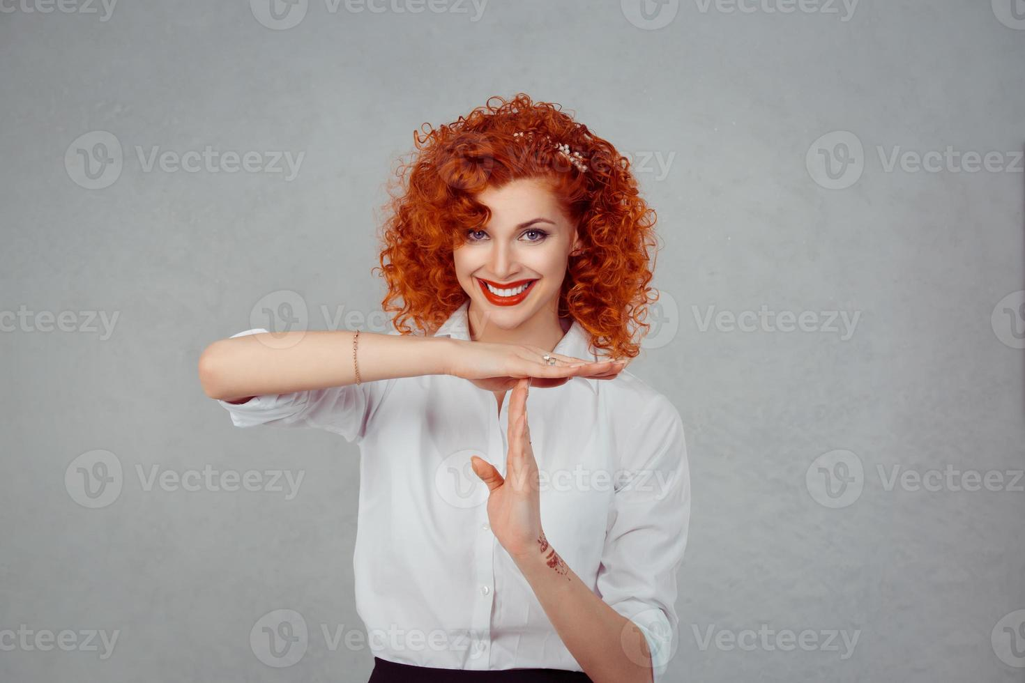 Timeout. Closeup portrait, young, happy, smiling woman showing time out gesture with hands isolated on gray wall background. Positive human emotion facial expressions, feeling body language reaction photo