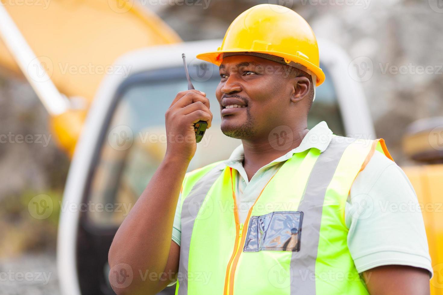 trabajador industrial afroamericano hablando por walkie-talkie foto