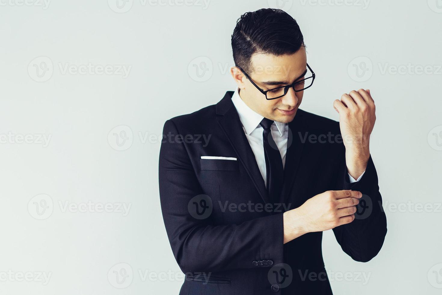 Serious fashionable young businessman buttoning jacket cuff photo