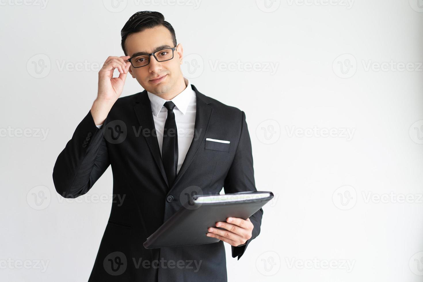 Serious handsome young businessman adjusting glasses photo