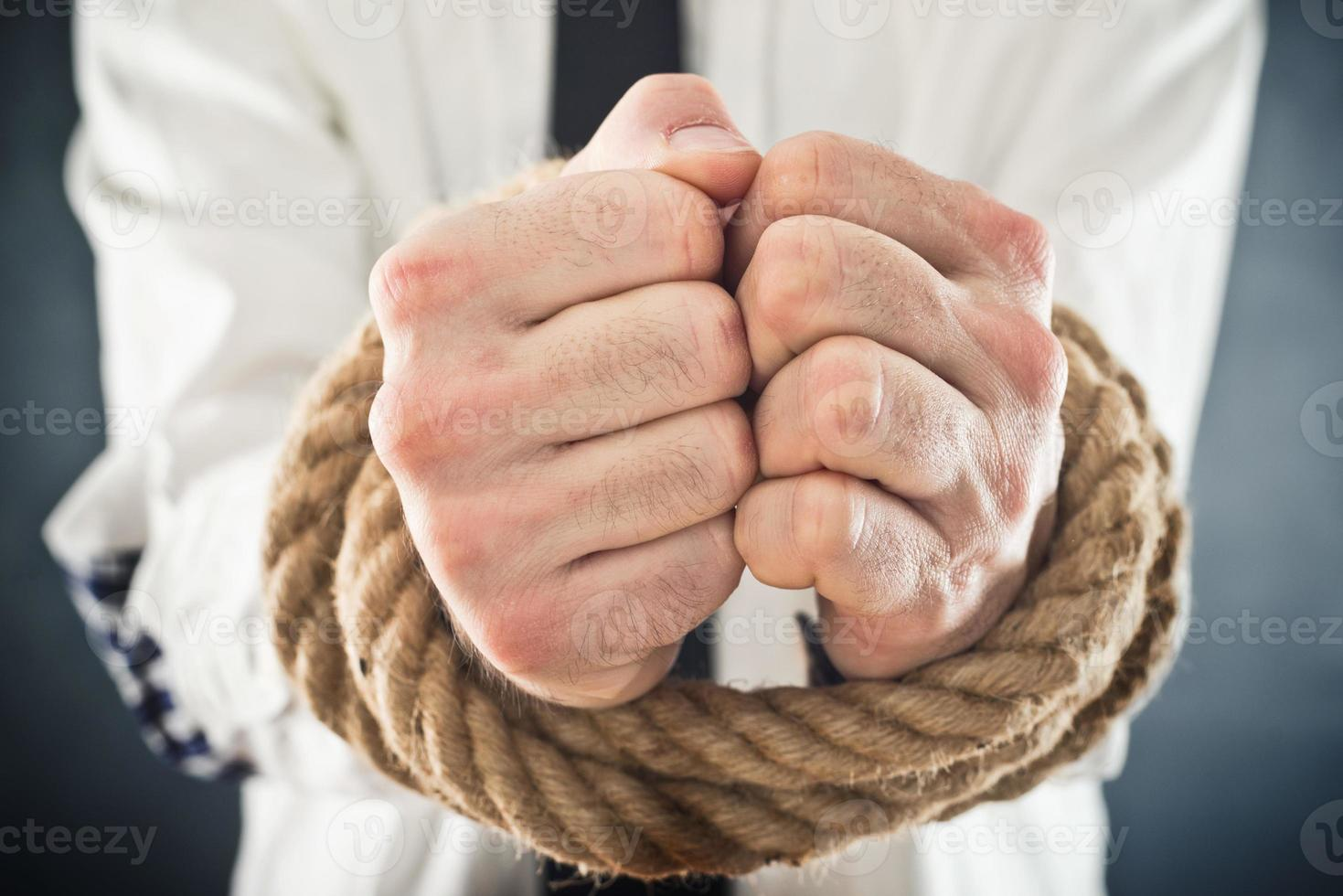 Businessman with hands tied in ropes photo